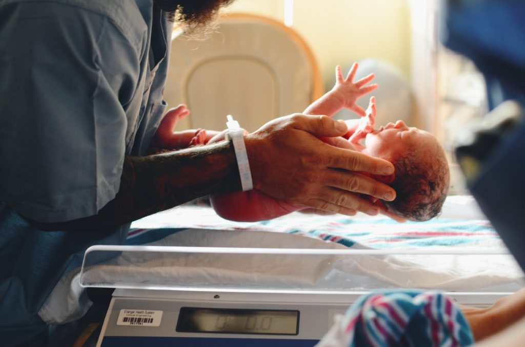 person wearing gray shirt putting baby on scale